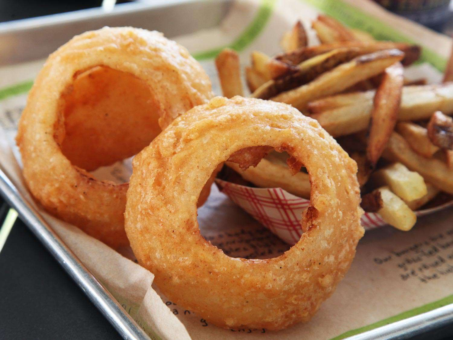 A serving tray with giant onion rings from Burger Fi and a paper container of french fries