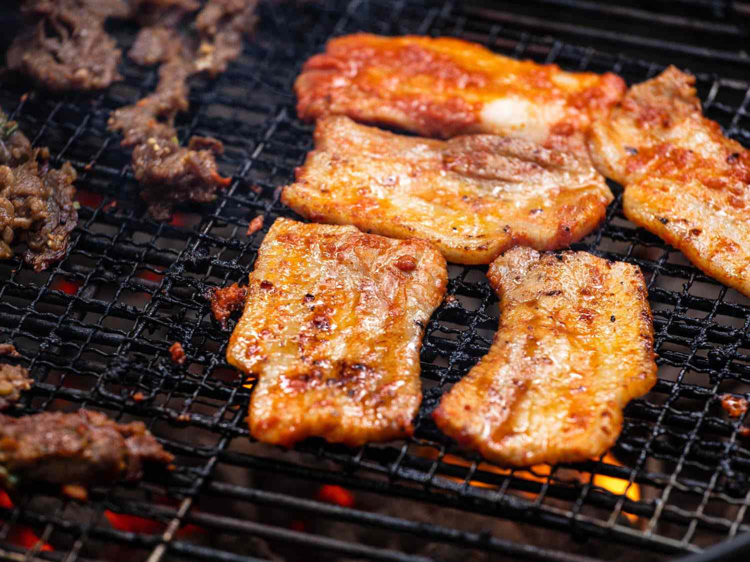 Closeup of pieces of pork belly on the grill.