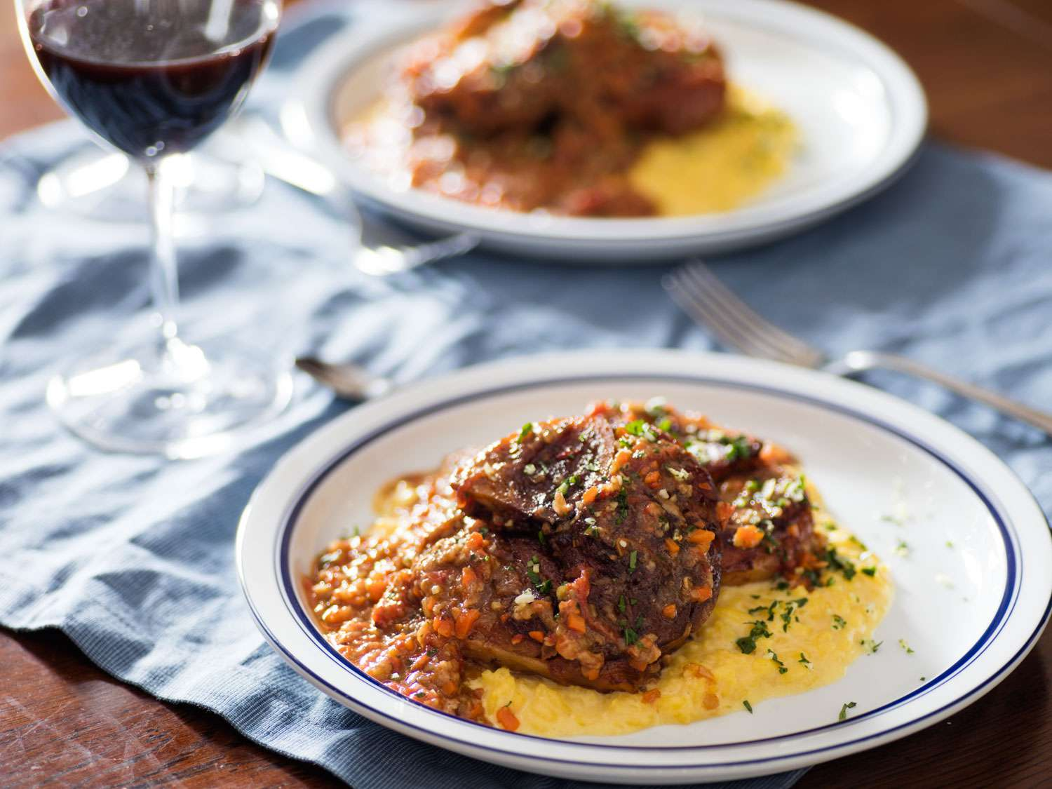Plate of osso buco on top of risotto alla milanese with second serving and glass of wine in the background.