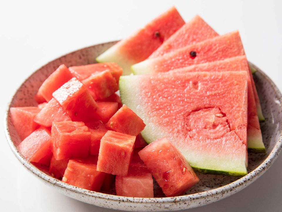 A bowl holding cubed watermelon and five watermelon wedges.