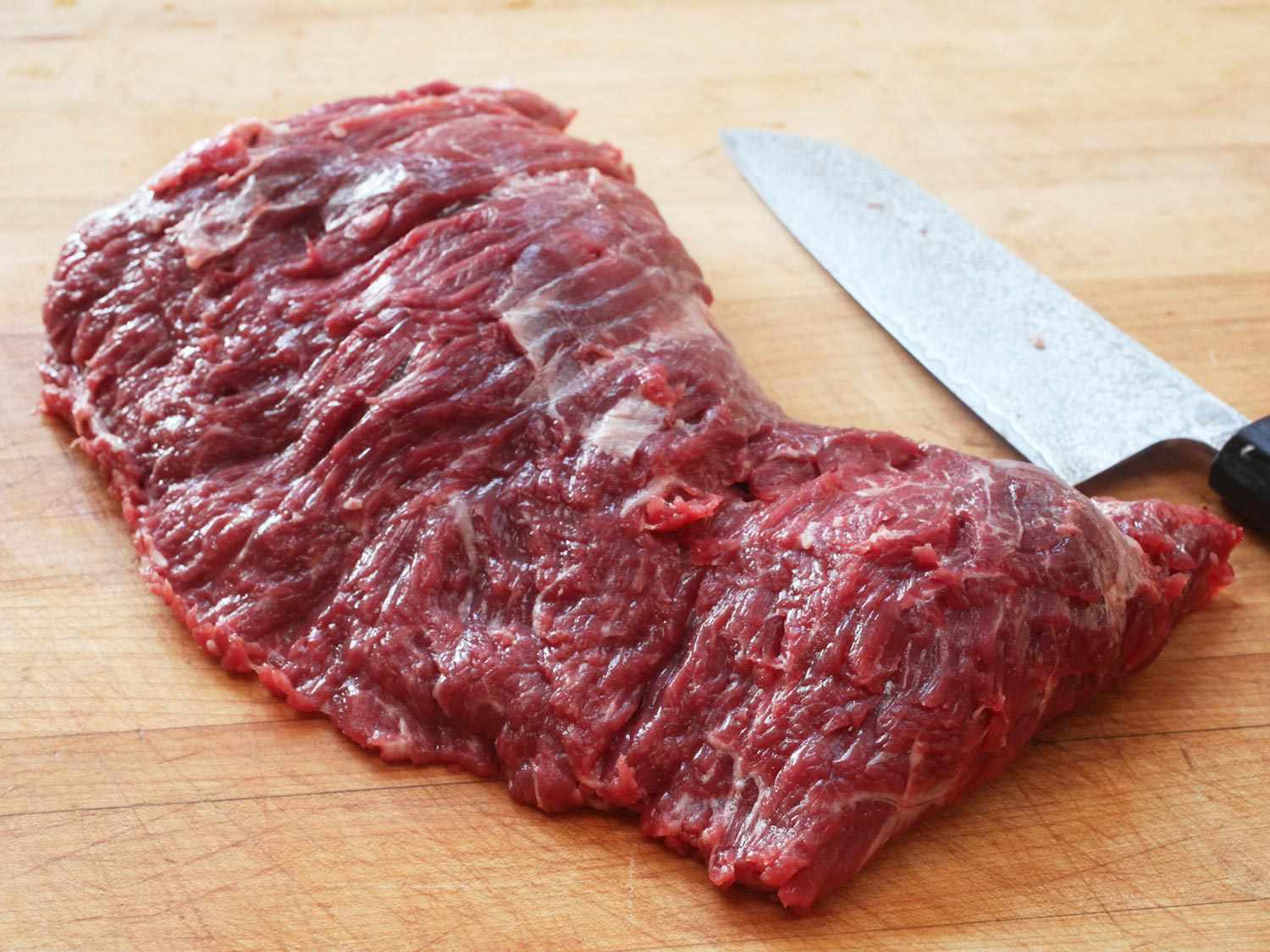 Raw flap meat steak on a wooden cutting board with a knife in the background.