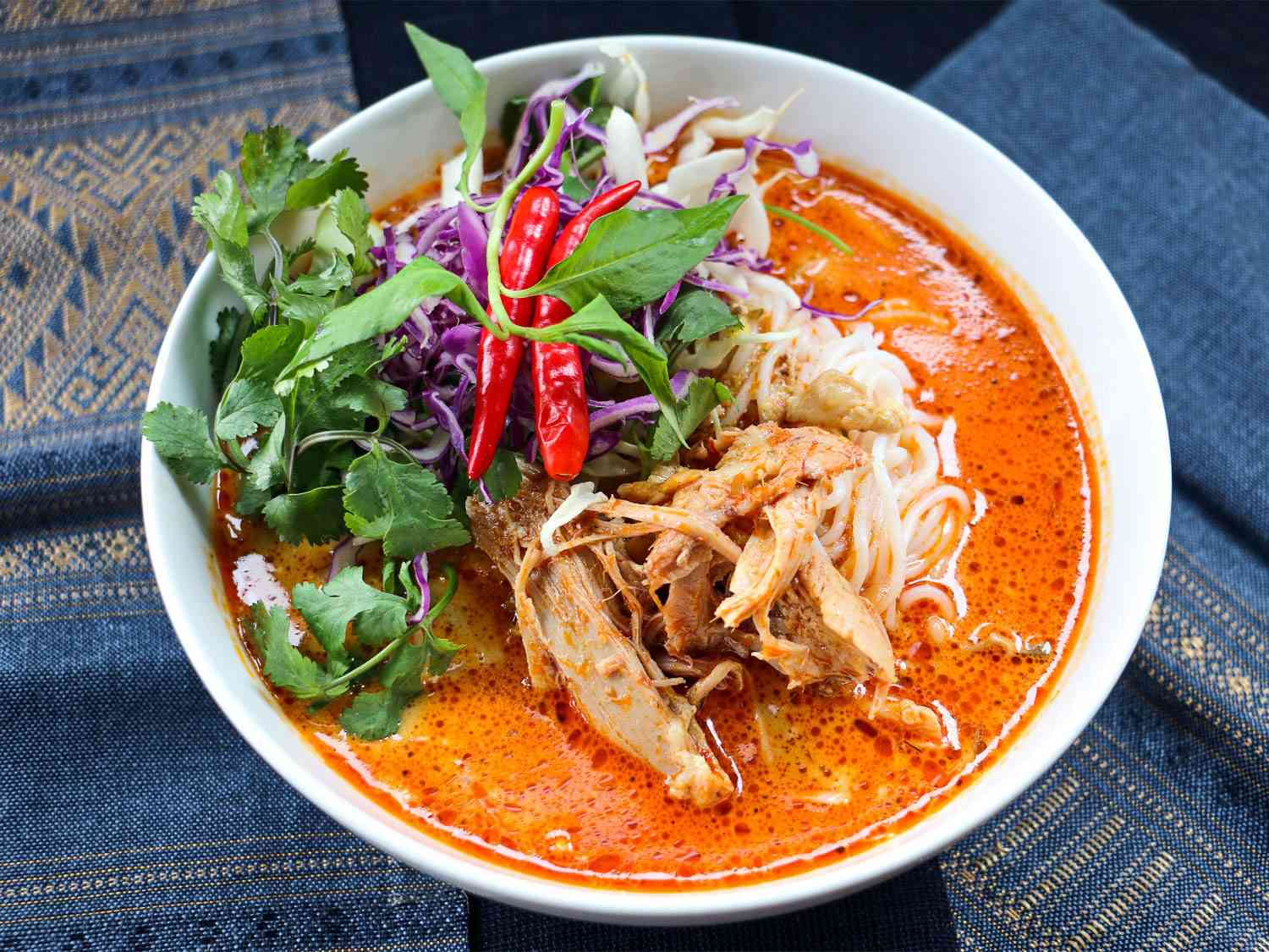 A bowl of khao poon: fermented vermicelli noodles in a bright red curry broth, with meat, herbs, red chilies, and purple cabbage