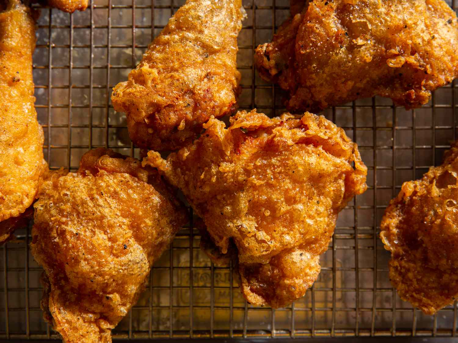 Batter-fried chicken pieces resting on a wire rack set in a rimmed baking sheet
