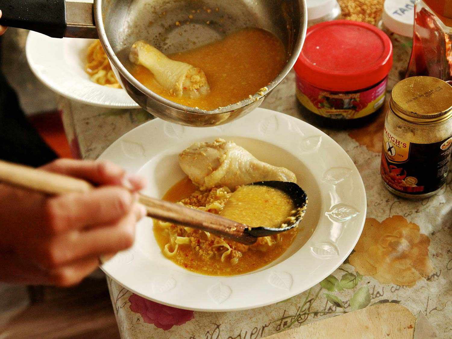 Scooping curry broth onto a white bowl of noodles with a chicken drumstick for Khao Soi Gai.