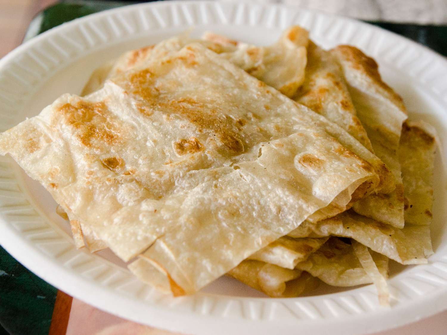 A small plate with a stack of roti.