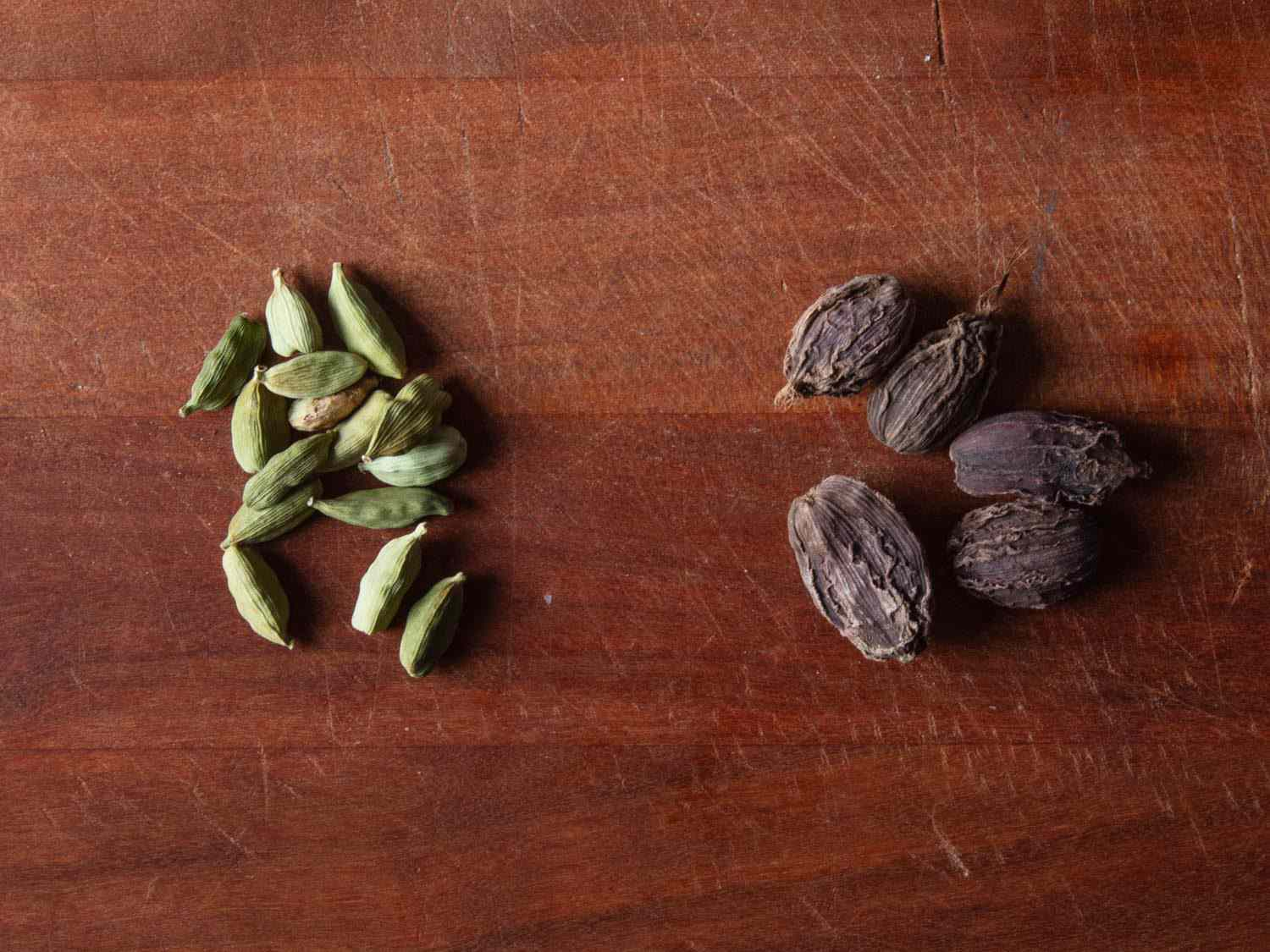 Side by side comparison of green cardamom pods (left) and brown cardamom pods (right)