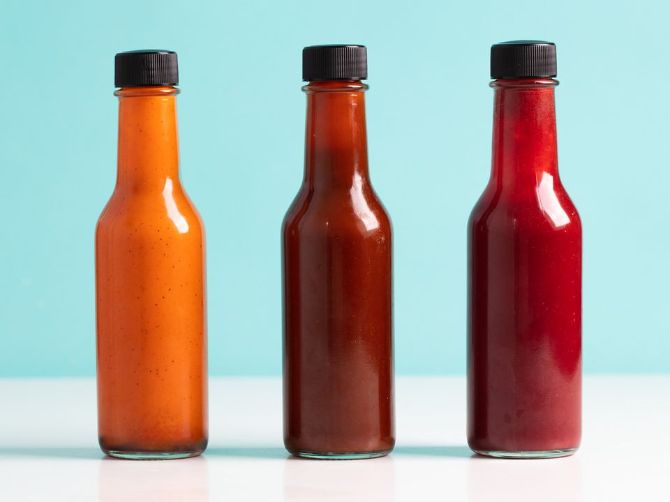 three different flavored fermented hot sauces in bottles