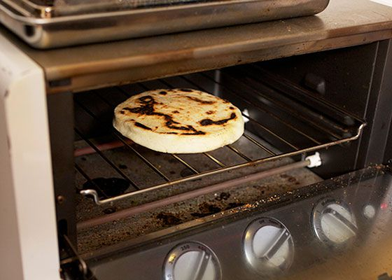 A cheese-filled arepa in an oven, cooking directly on the oven rack.