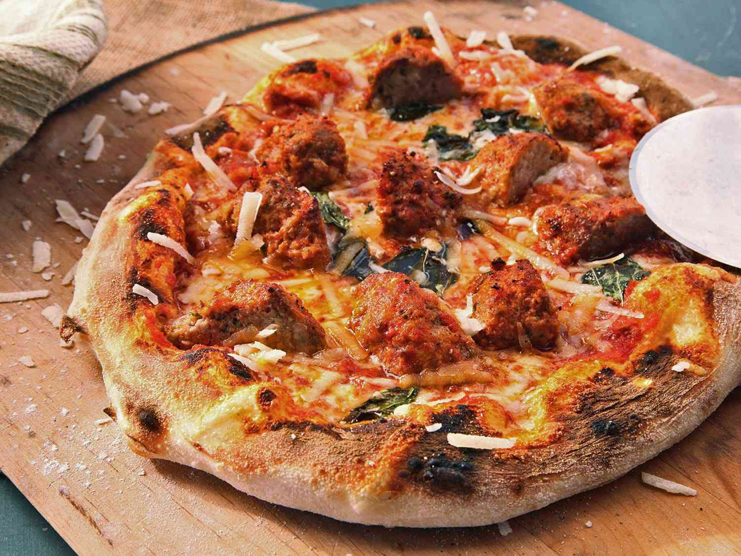 A small pizza topped with quartered large meatballs, on a wooden surface
