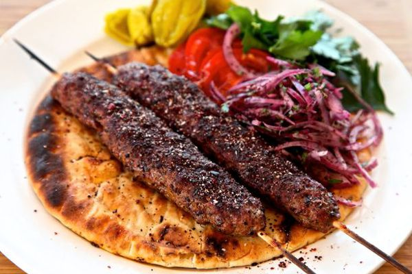 Two adana kebabs on a plate with flatbread, sumac onions, parsley, tomatoes, and pickled peppers.