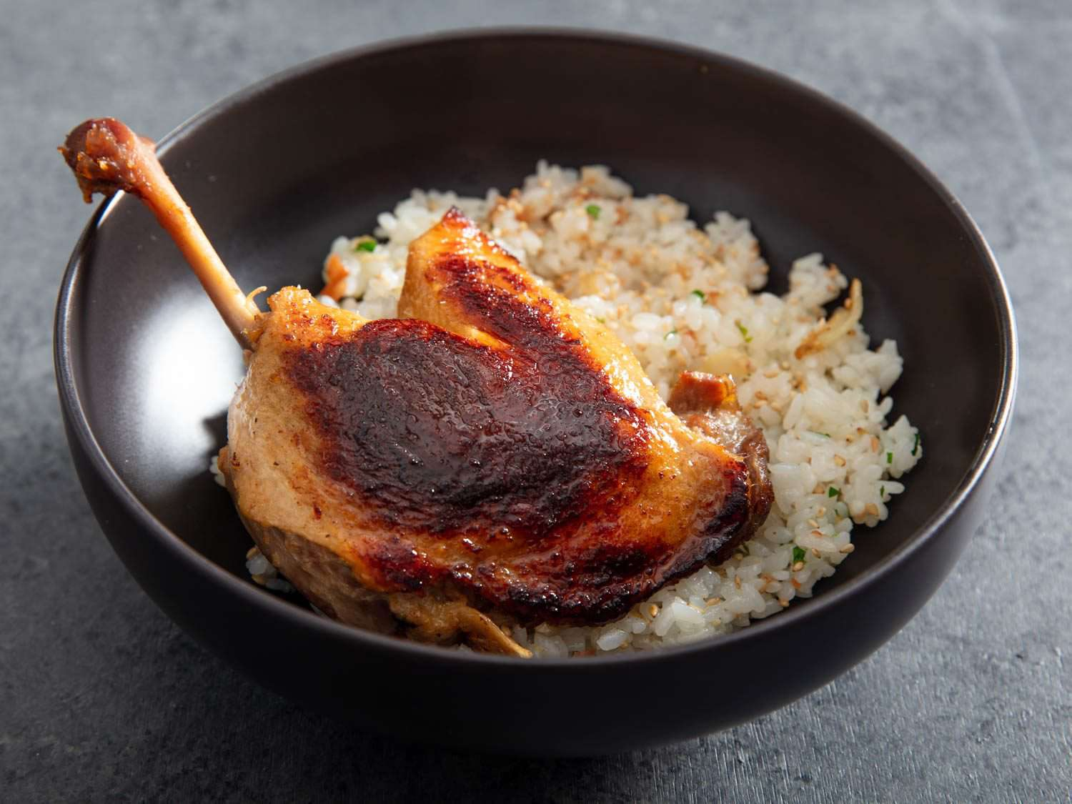 Closeup side view of a crisped koji confit duck leg in a bowl with rice.