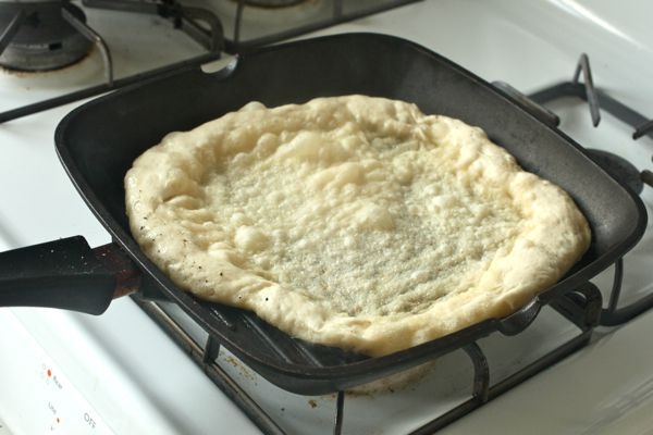 pizza dough on grill pan on stovetop