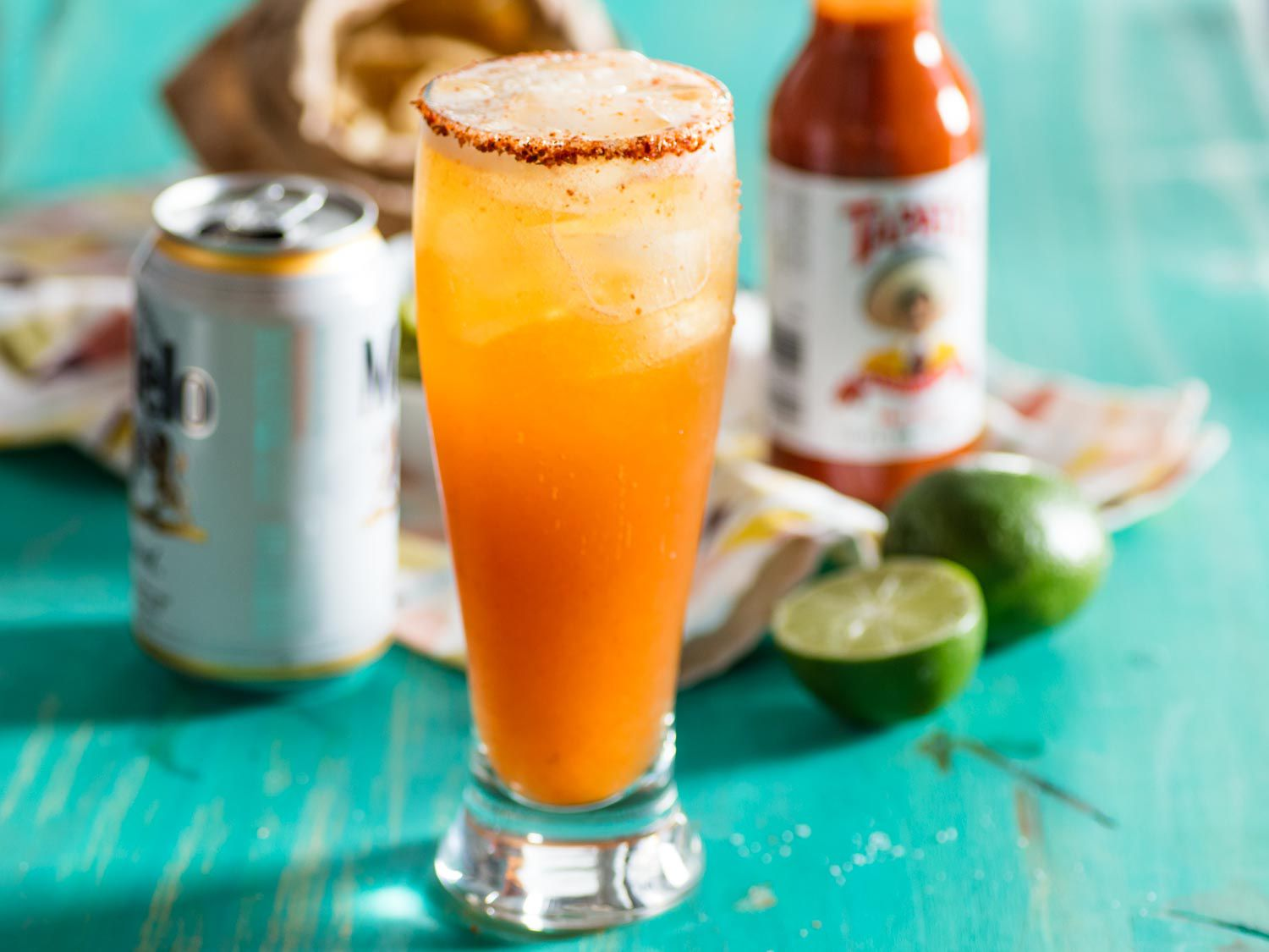 A finished michelada in a tall glass, with an open beer can, bottle of hot sauce, and halved lime in the background