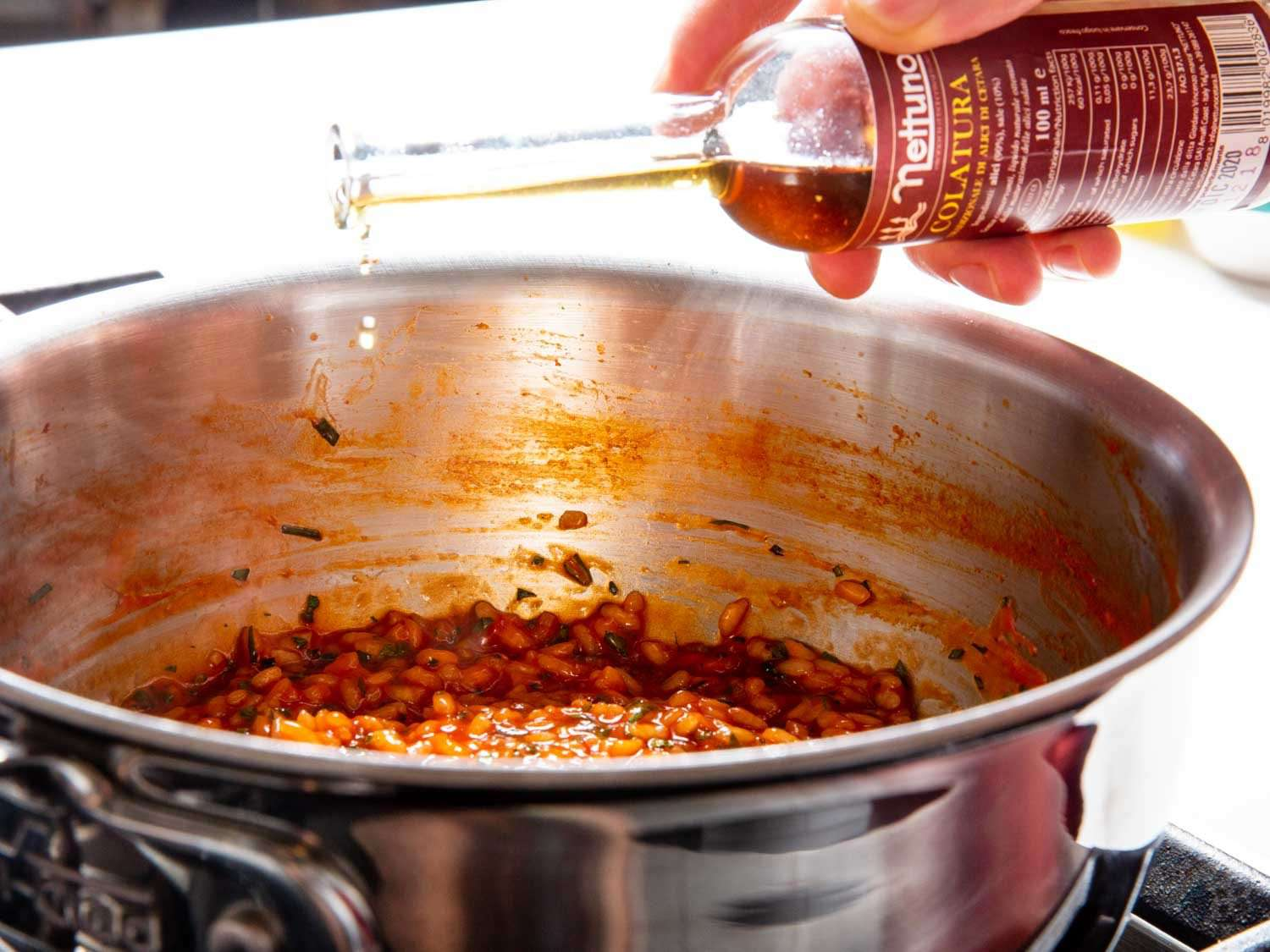 Adding a few drops of colatura fish sauce to the par-cooked rice. This step is optional.