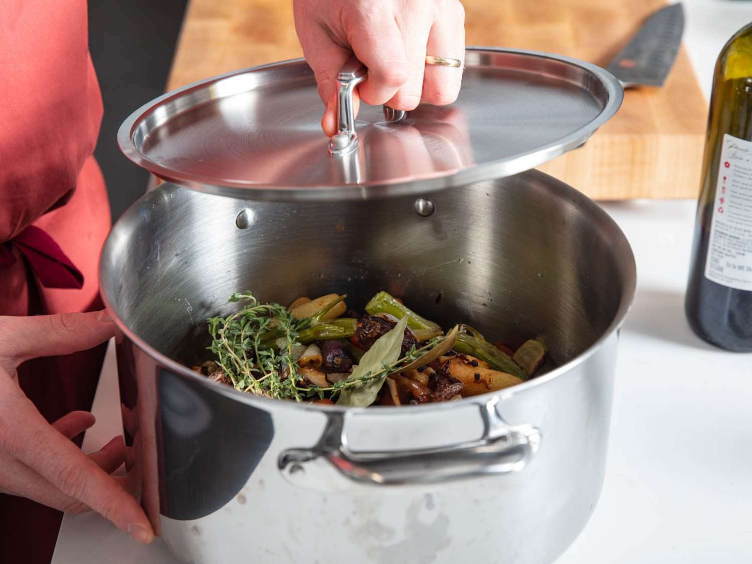 Popping a lid on a stockpot with all ingredients for duck stock except for water. Stockpot can be refrigerated until you are ready to make stock and then all you need to do is add water and cook on the stovetop.