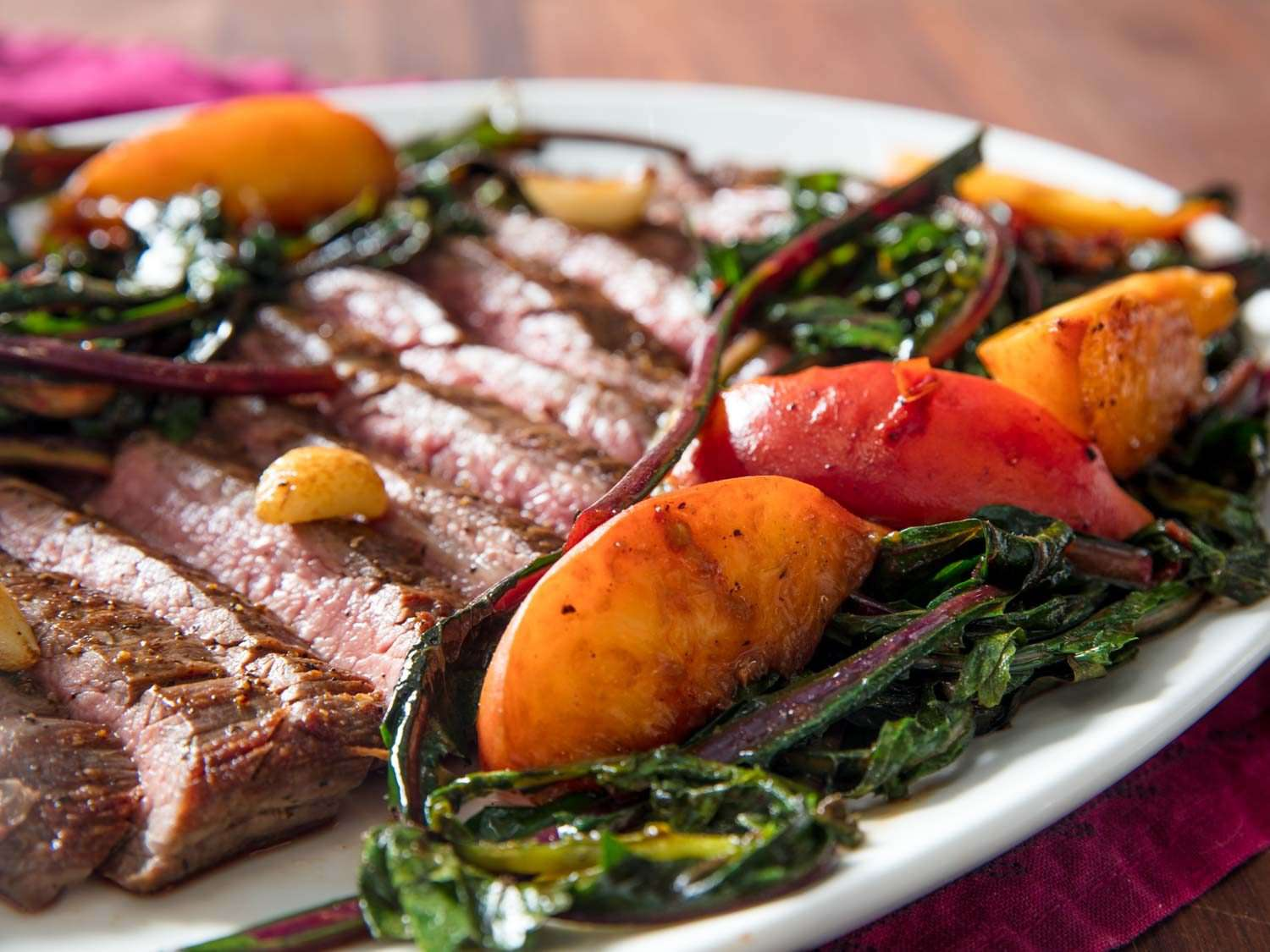 Close-up of sliced pan-seared flank steak accompanied by seared whole garlic cloves, seared peach slices, and wilted dandelion greens, on a white dish