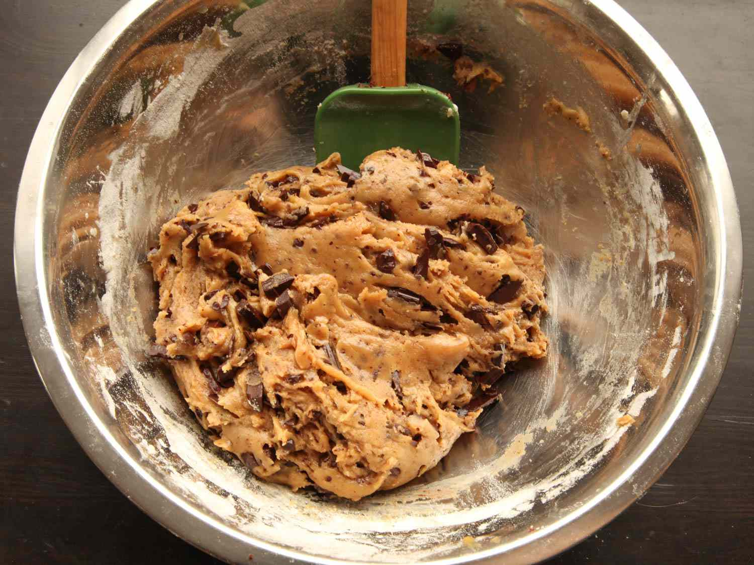 Bowl of cookie dough made by over-mixing in the flour for tough, smooth-textured cookie.