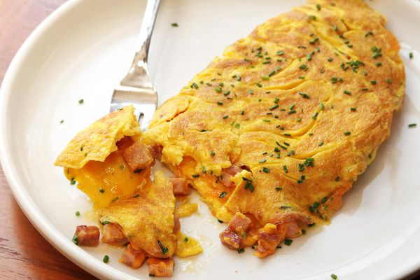 A diner-style ham and cheese omelette on a white plate, sprinkled with chives. A fork is lifting a bit of the omelette.-american-omelet-ham-and-cheese-23.JPG