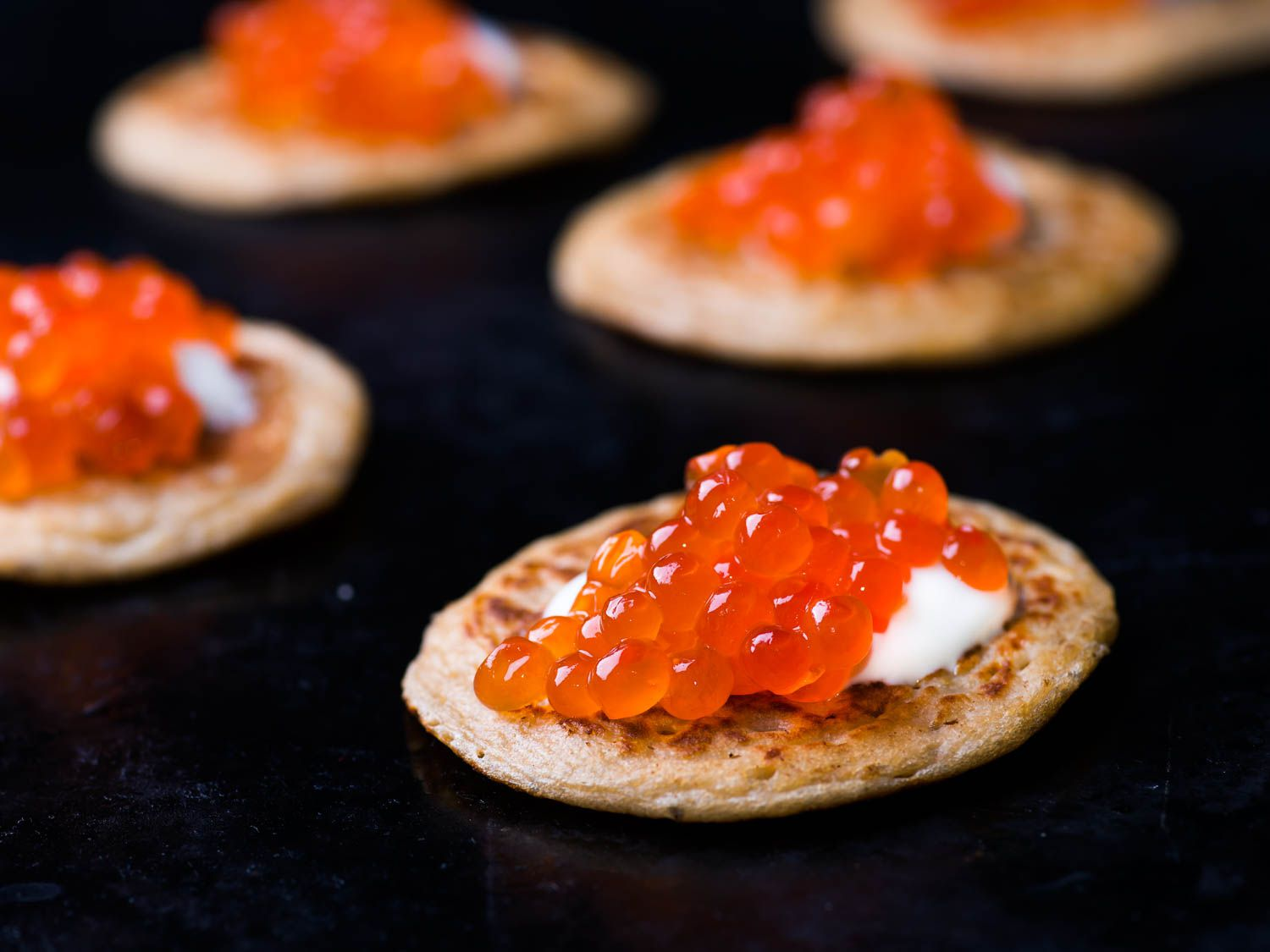 Blini topped with sour cream and caviar.