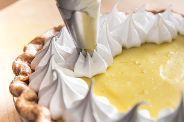 Piping whipped cream on top of a lemon meringue pie.