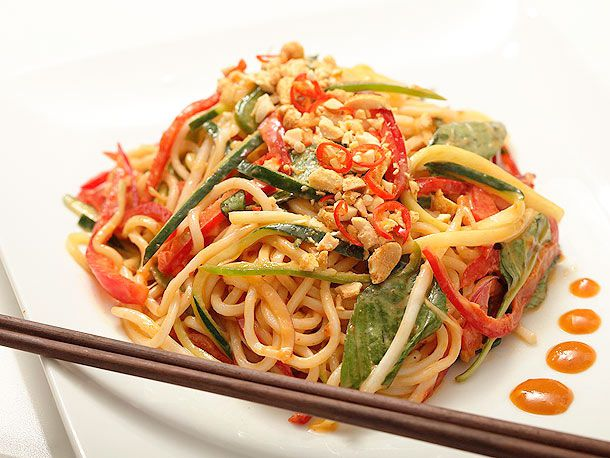 A white dish of Spicy Peanut Noodle Salad With Cucumbers, Red Peppers, and Basil, with a pair of chopsticks