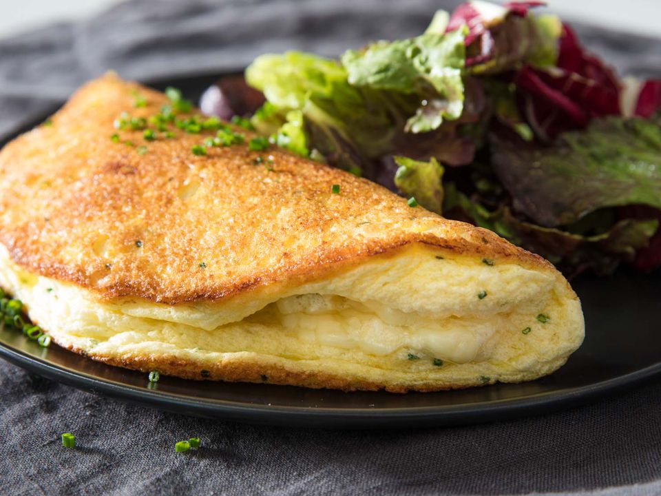 Soufflé omelette on a black plate with mixed green salad on the side.
