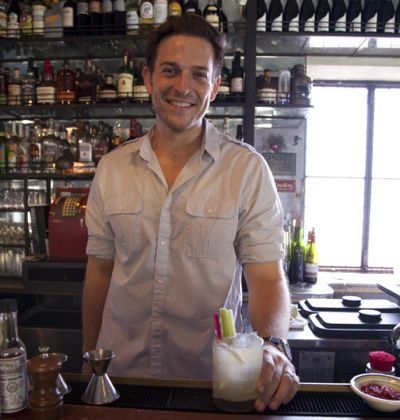 Bartender behind the bar, holding a cocktail