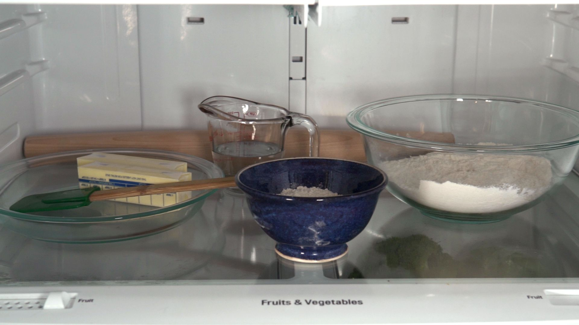 Refrigerator shelf with a glass pie dish holding a spatula and two sticks of butter, a glass measuring cup of water, a blue ceramic bowl, and a glass mixing bowl with flour