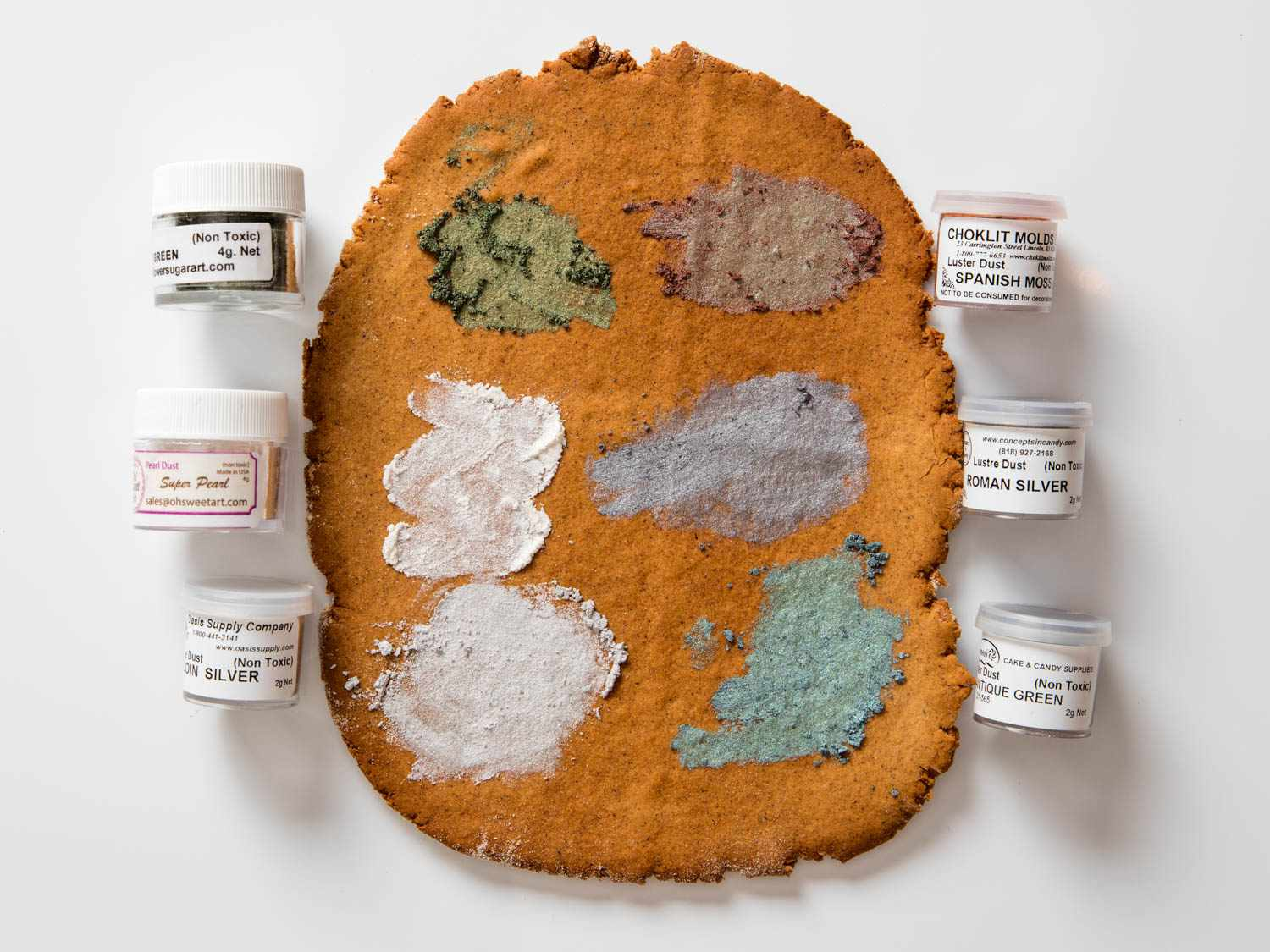 Samples of luster dust in various dull colors, against a slab of gingerbread