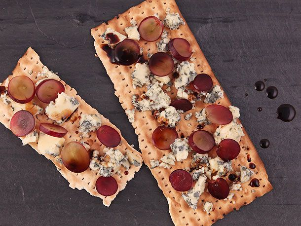 A piece of matzo layered with crumbles of blue cheese, sliced grapes, and drizzles of balsamic vinegar syrup