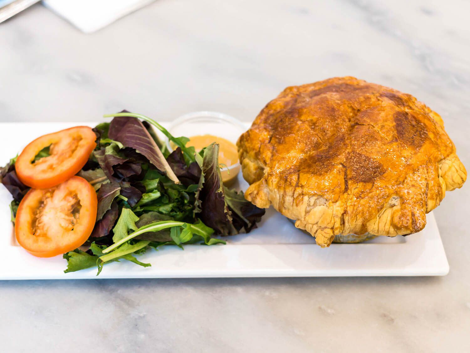 A golden-crusted pot pie on a plate next to greens and sliced tomato