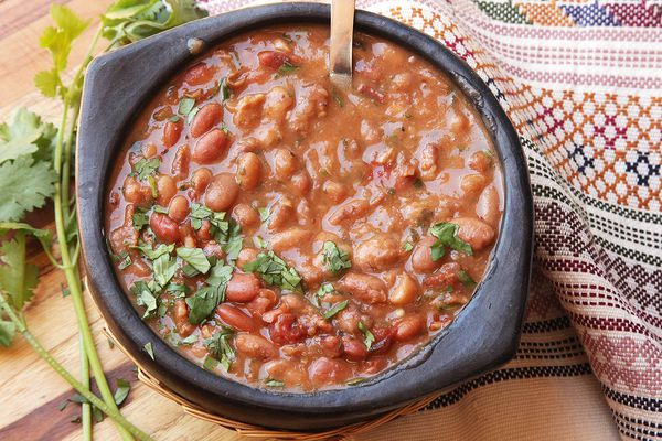 A bowl of frijoles charros, Mexican cowboy beans, topped with cilantro.