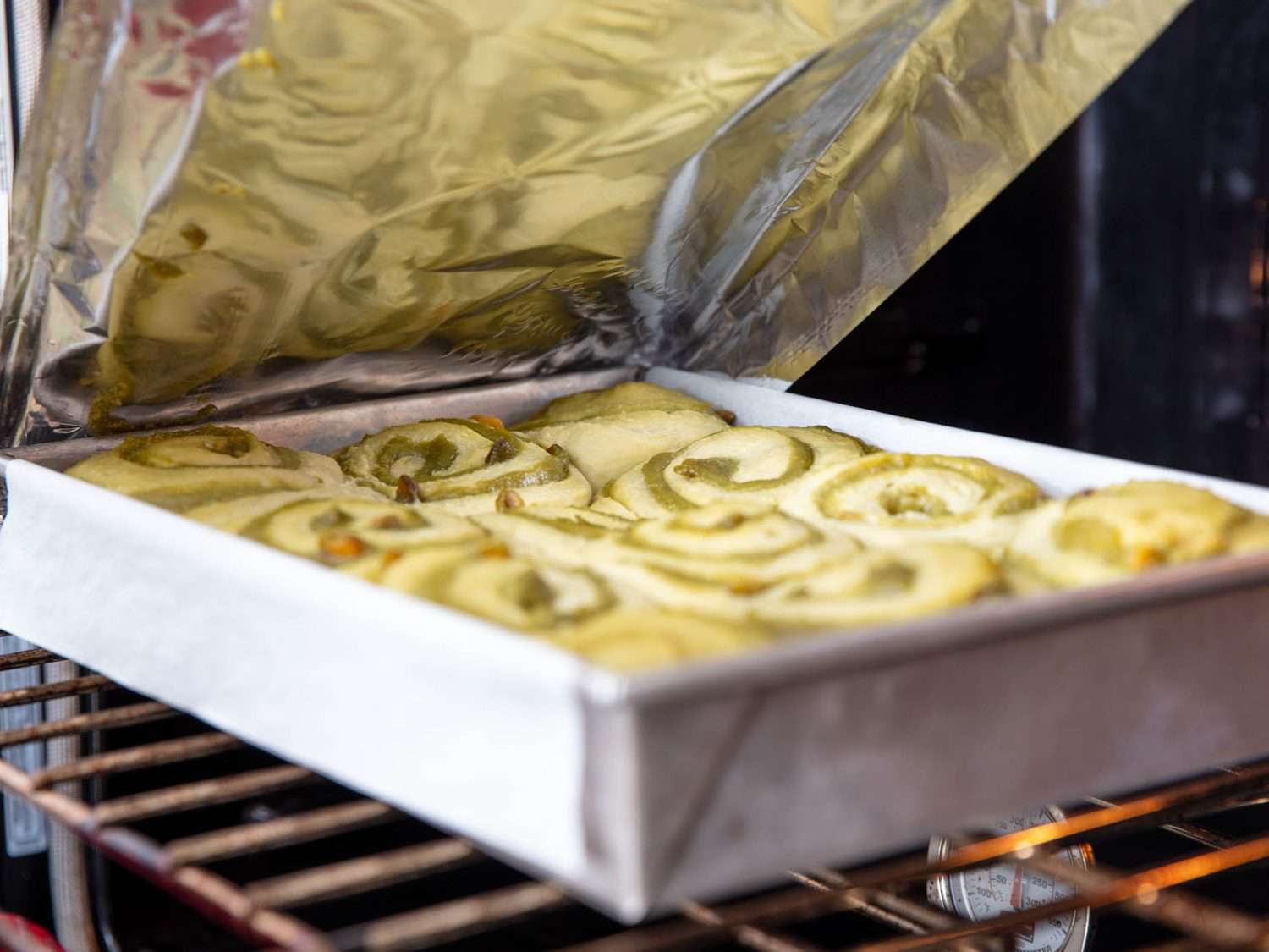 removing the foil on pale and puffy, semi-baked pistachio buns
