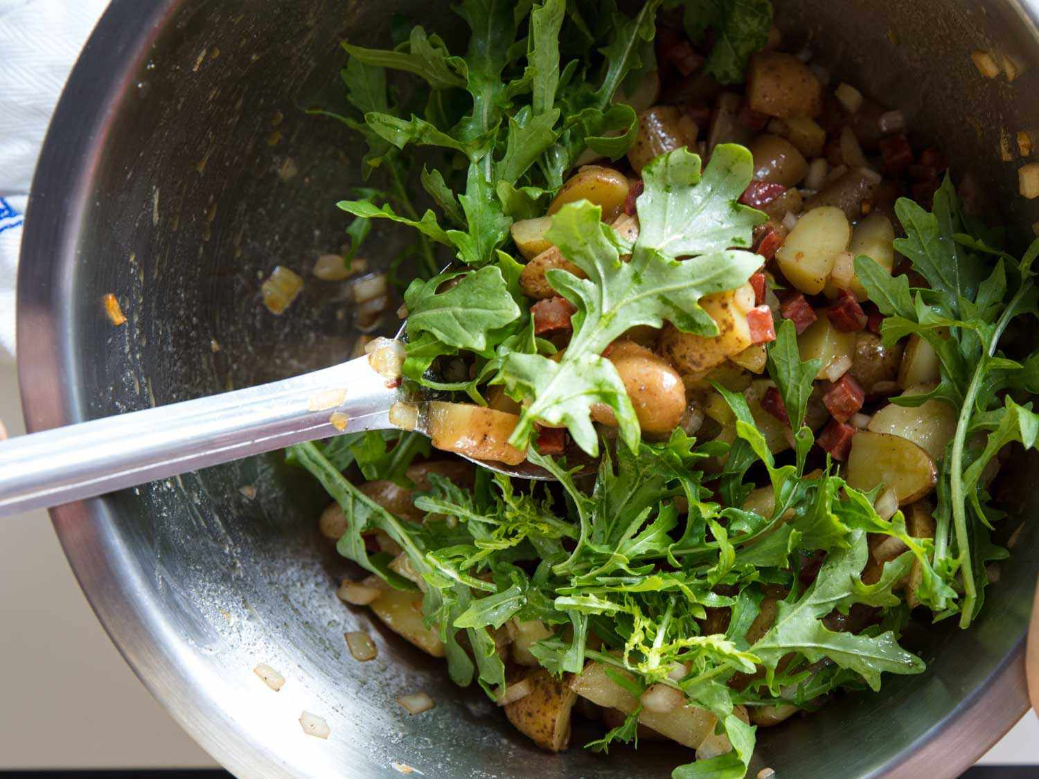 Mixing arugula leaves into a bowl of fingerling potatoes, sautéed onion, pickled onion, and diced chorizo