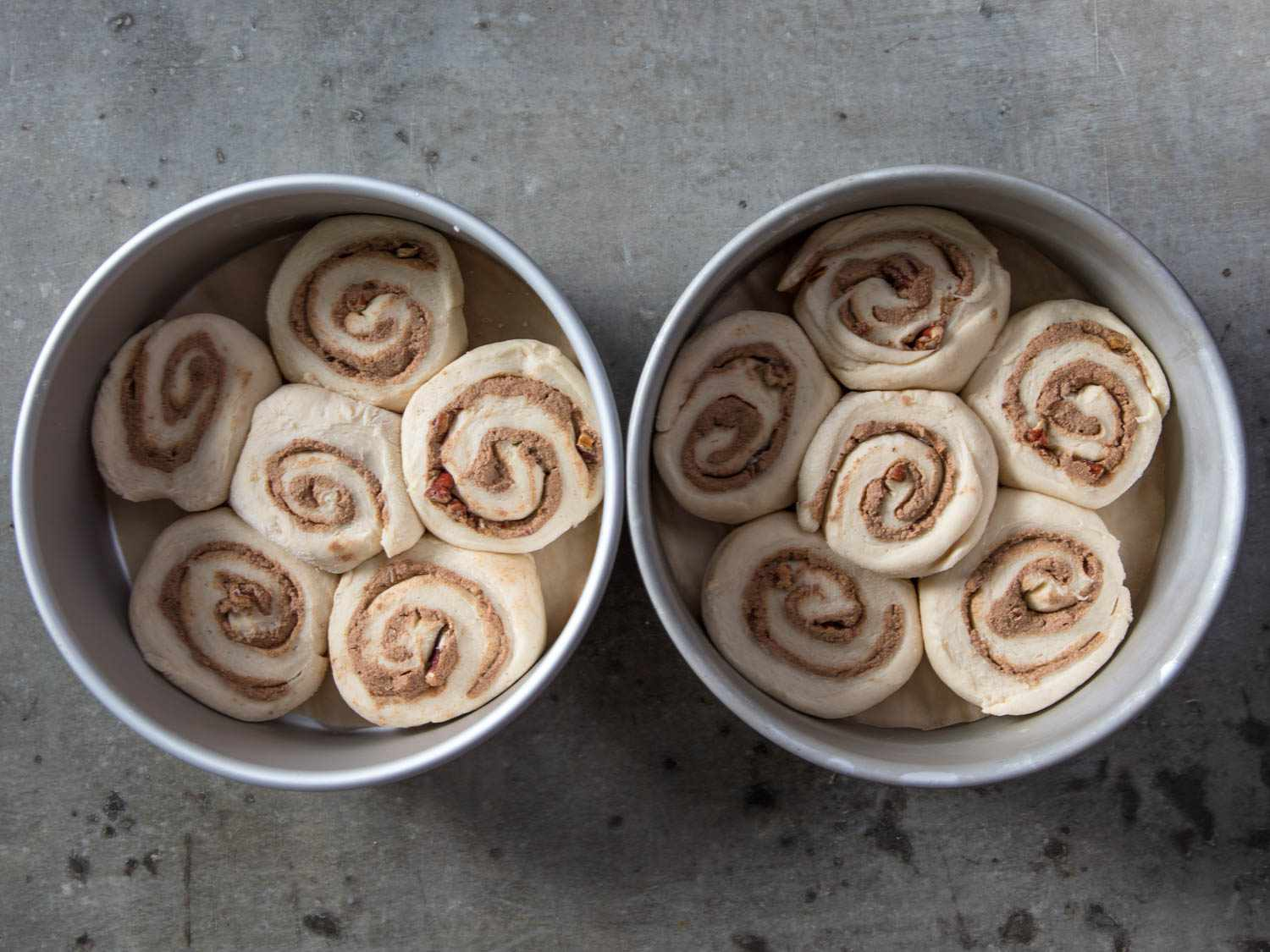 Overhead shot of prepared, unbaked cinnamon rolls in two round cake pans