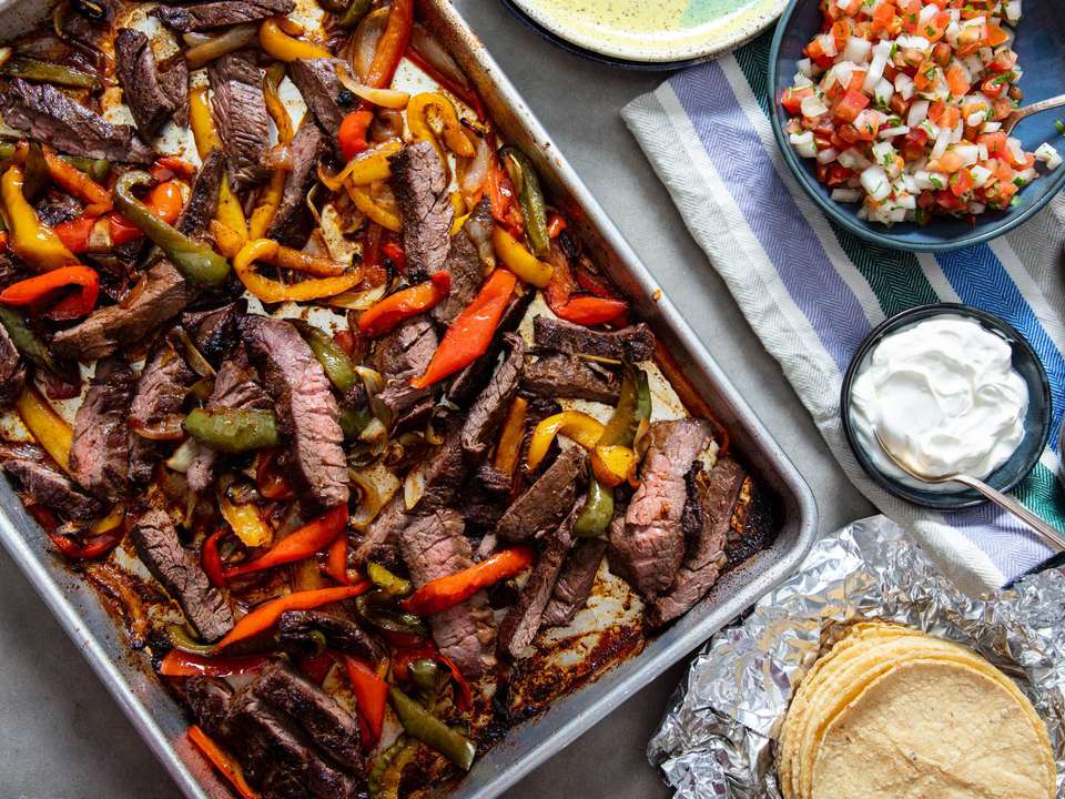 A sheet pan loaded with skirt steak strips, bell peppers, and onions, all after being cooked until charred, ready to be loaded into tortillas for fajitas