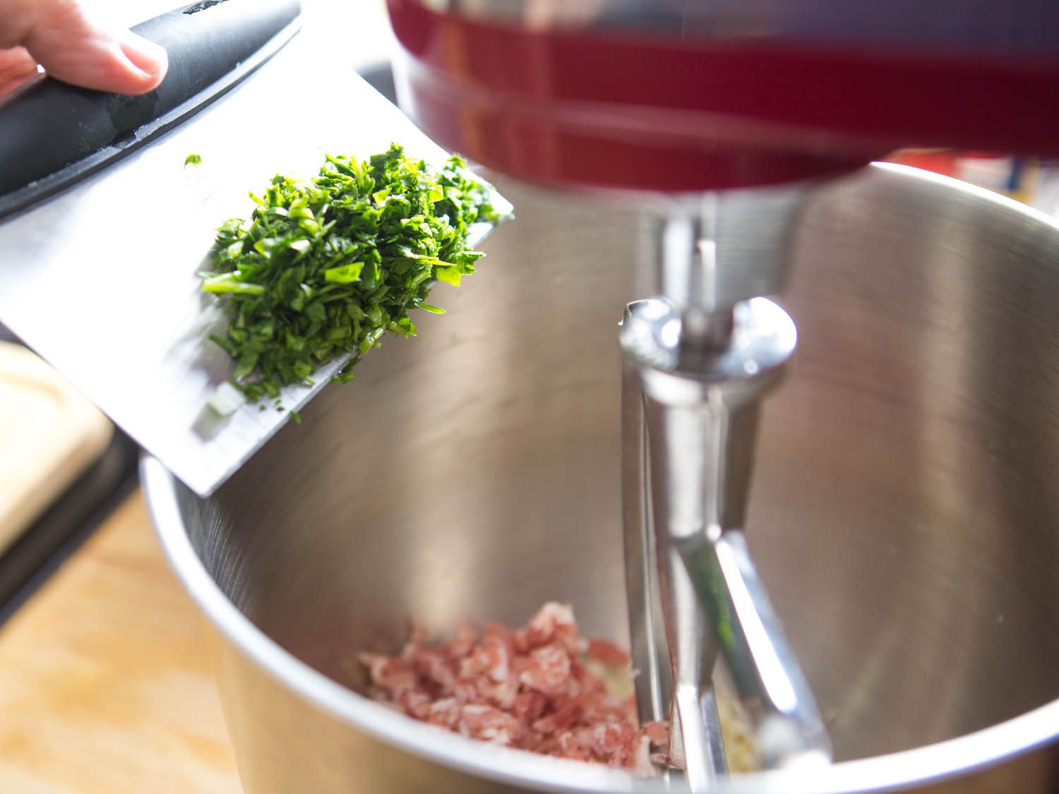 Adding chopped parsley to bowl of stand mixer for meatballs.