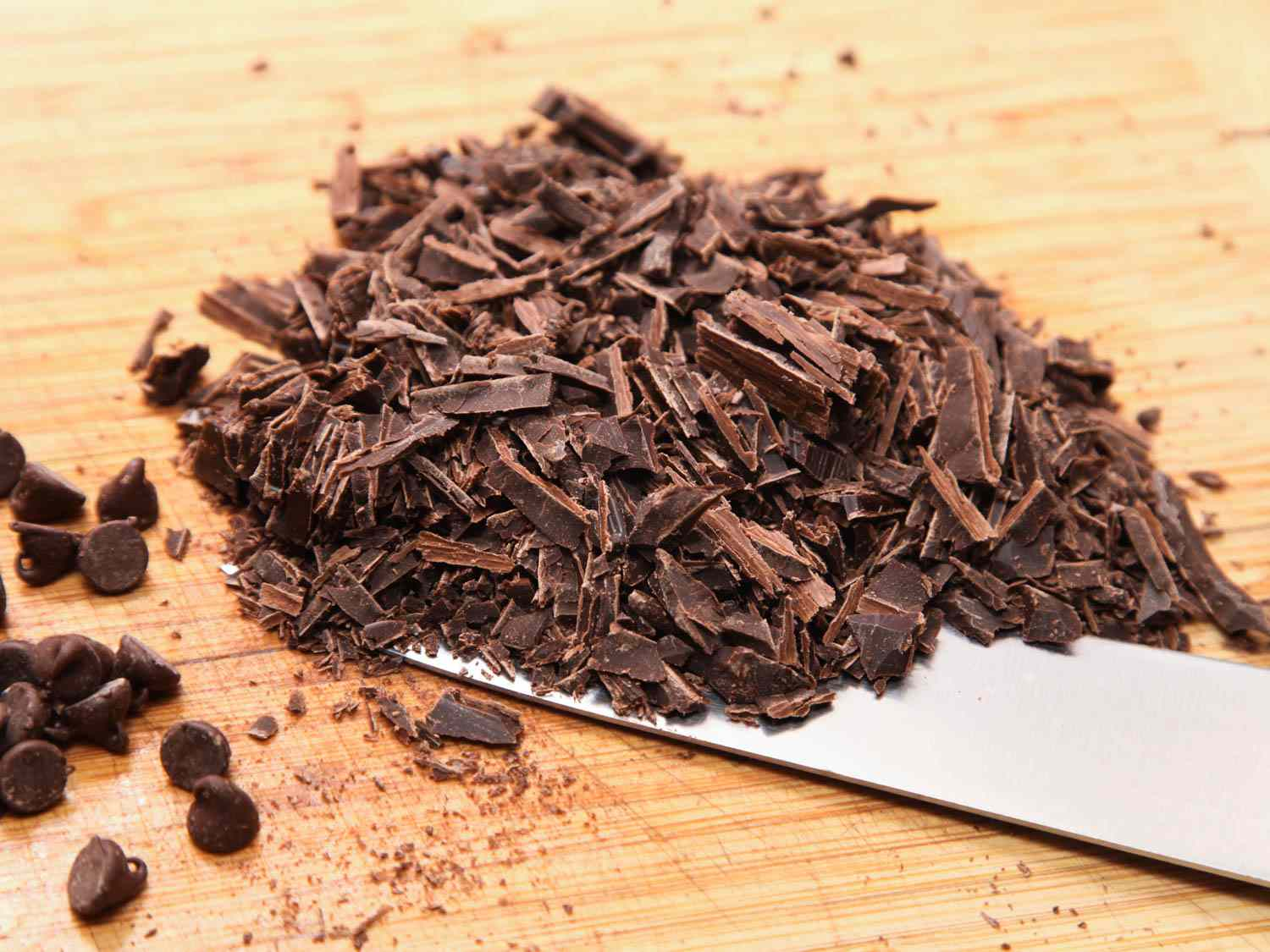 A pile of chopped chocolate on a cutting board next to a few chocolate chips.