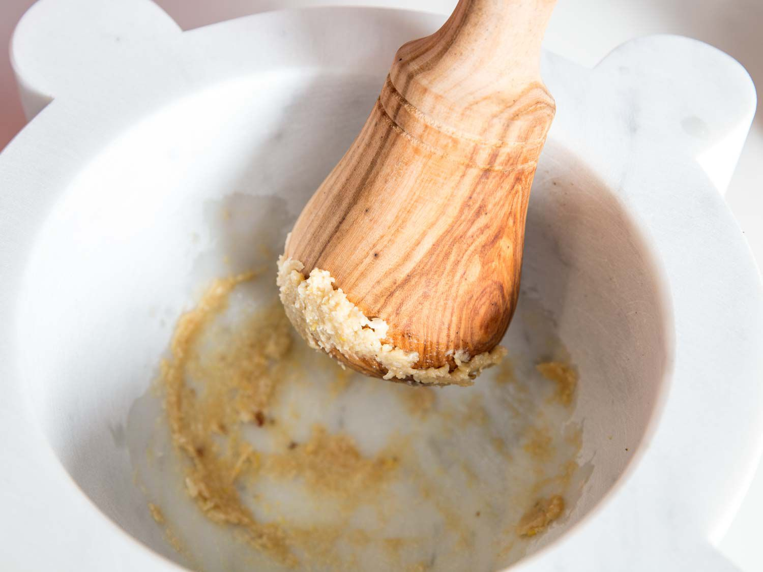 Pounding garlic to a paste using a marble mortar and wooden pestle.