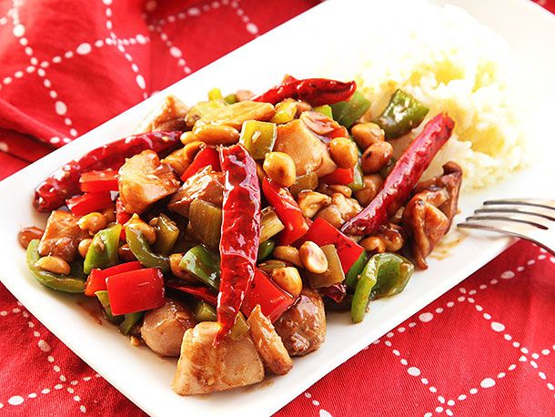 Takeout-style kung pao chicken on a white rectangular plate with rice on the side.