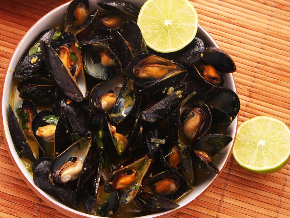 Overhead shot of mussels steamed in Thai curry/coconut broth, with lime halves