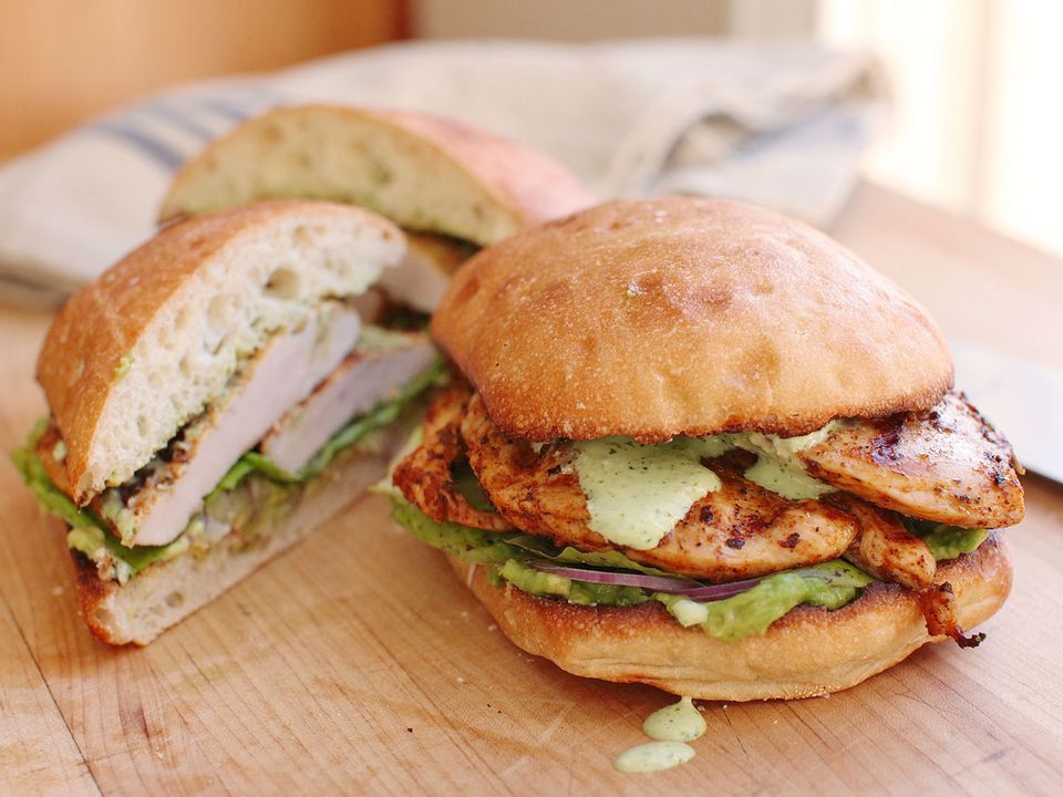 A Peruvian grilled chicken sandwich topped with avocado, red onion, and green sauce, with two sandwich halves nearby