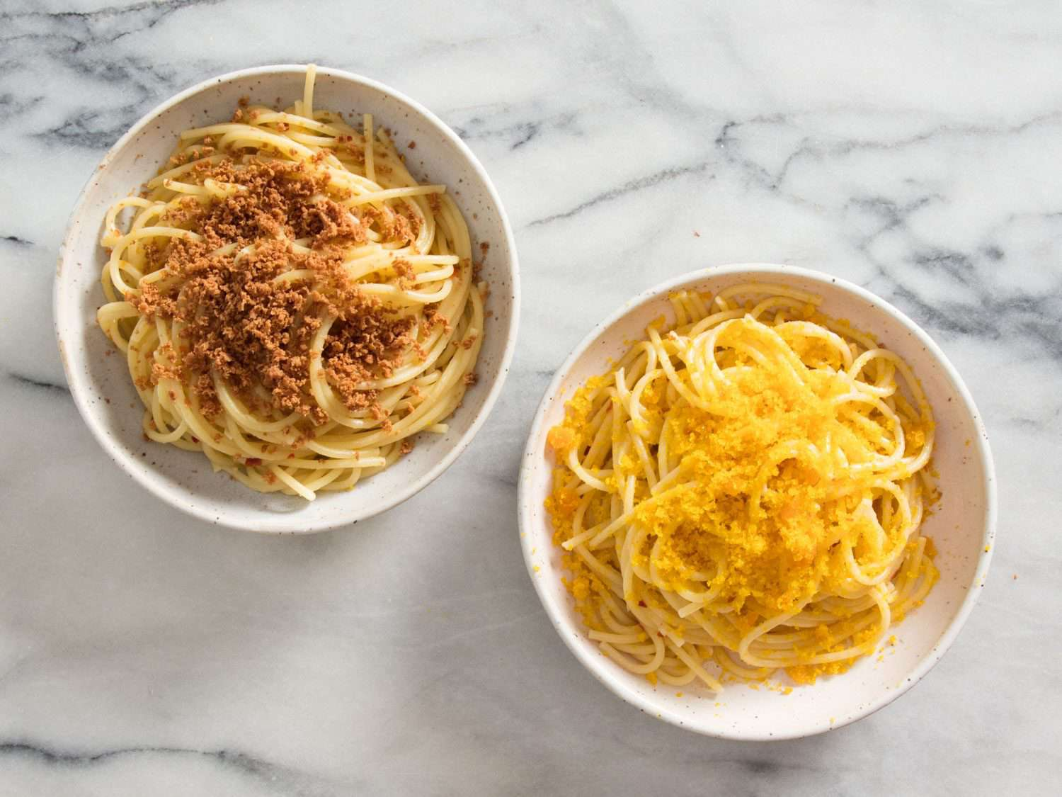 Two bowls of pasta side by side, with tuna bottarga grated over bowl on left, and mullet bottarga grated over bowl on right
