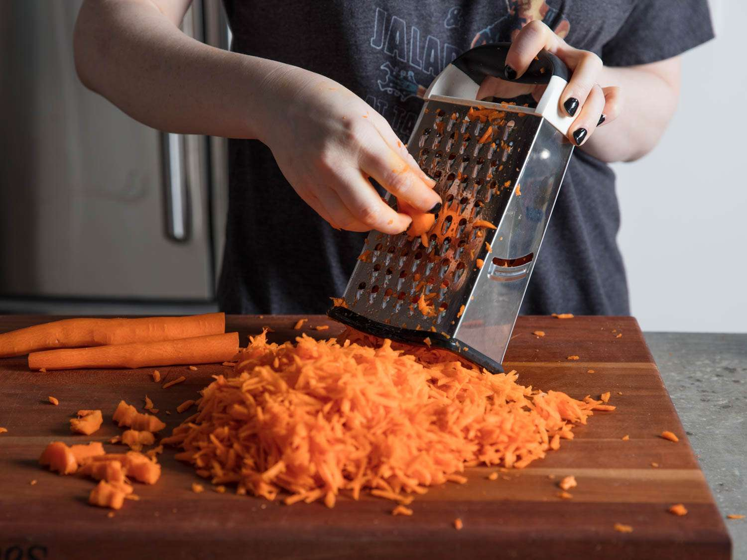 Grating carrots on the holes of a box grater, on a wooden cutting board