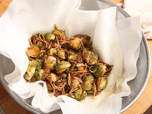 Already fried Brussels sprouts and shallots draining on a paper towel in a silver bowl.
