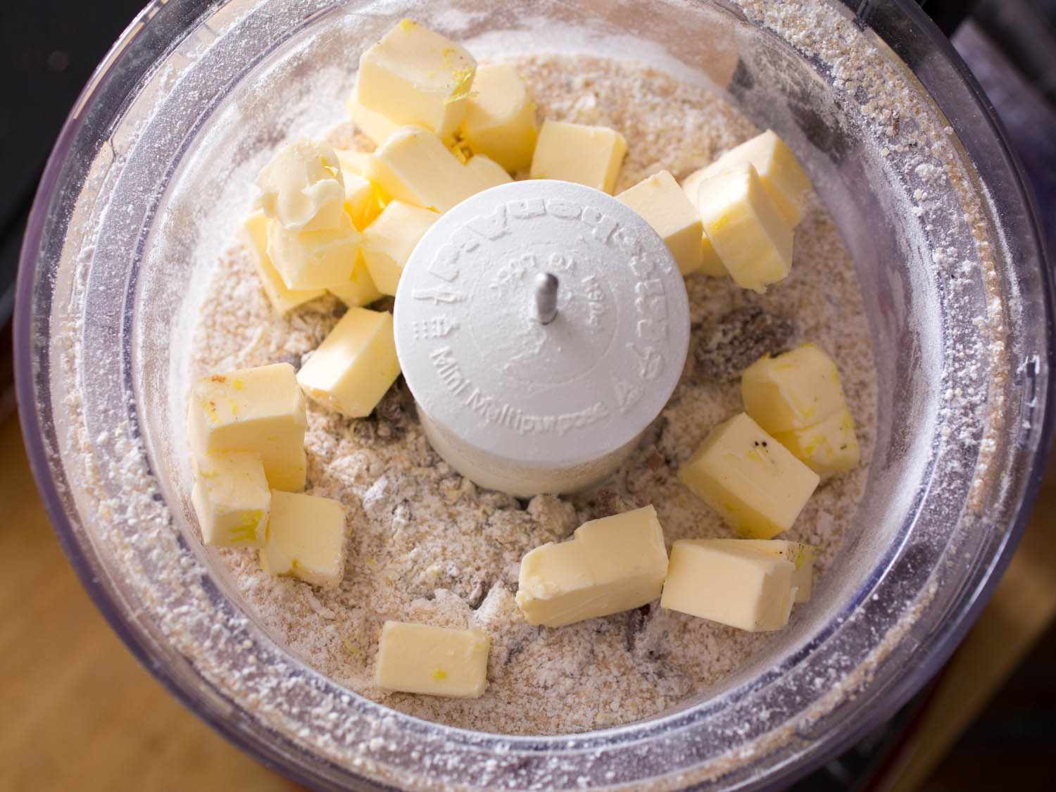 Overhead shot of food processor bowl of dry ingredients for crumb topping, with chunks of butter on top