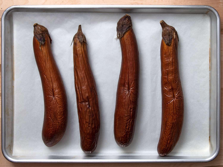 4 roasted eggplants on a baking sheet