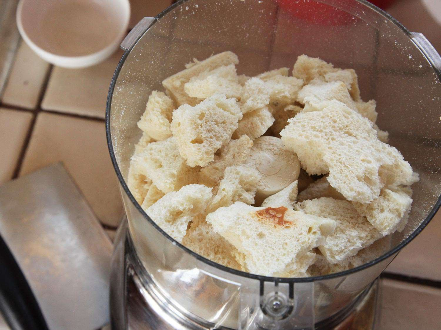 Crustless dehydrated craggy bits of bread in food processor bowl