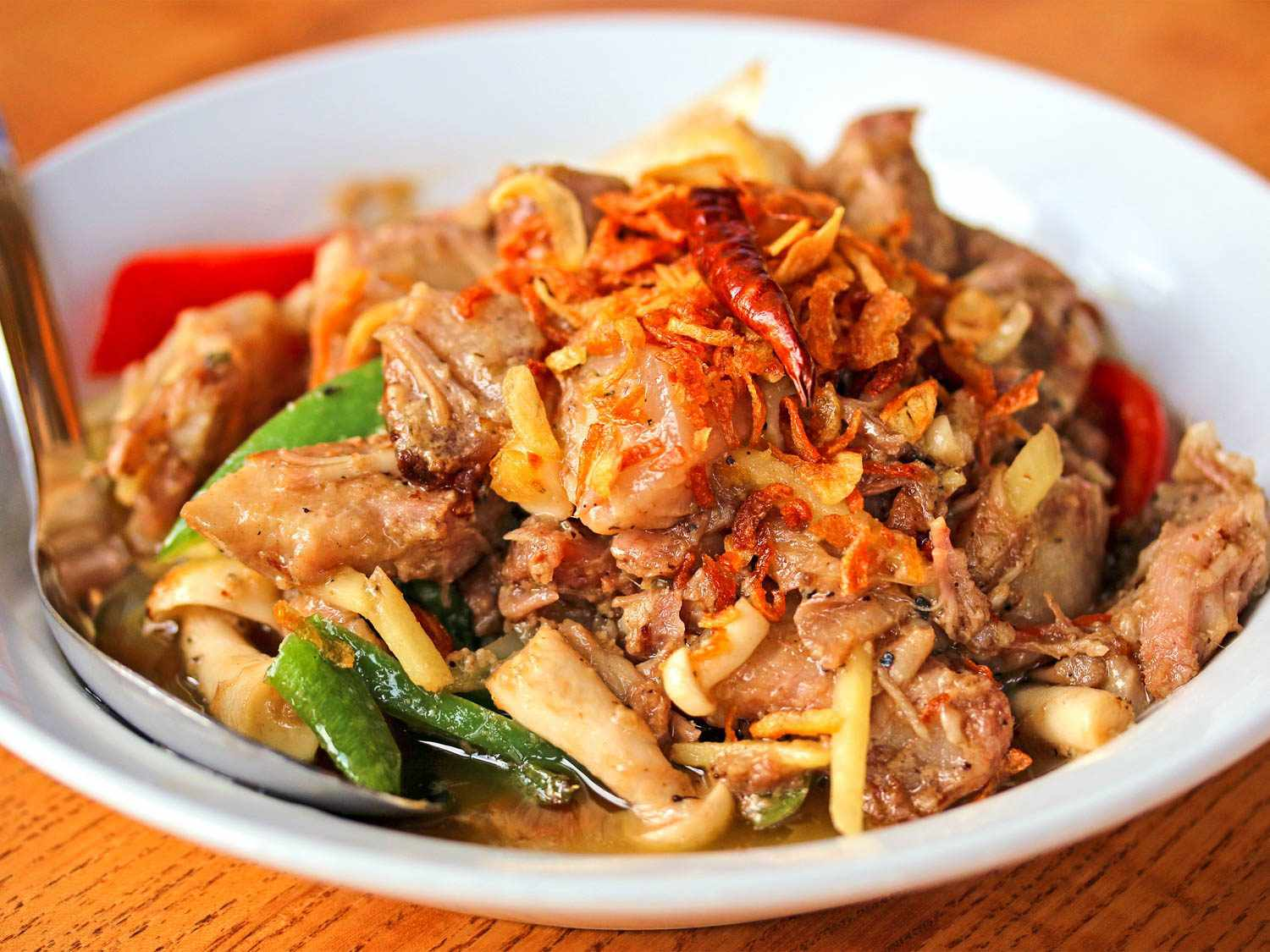 A plate of muu som: fermented pork belly with chilies and fried shallots
