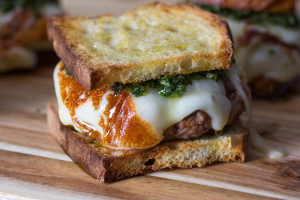 Three asado burgers on a wood cutting board, each made on sliced bread and topped with melted cheese and chimichurri.
